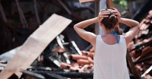Woman Looking at Destroyed Building Loss After Disaster